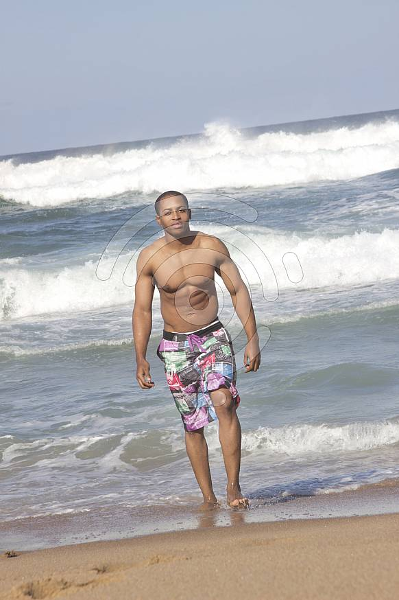 Black man walking out of the shallow waves on the beach