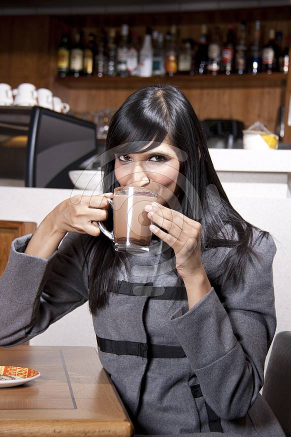 Woman sipping hot chocolate at a coffeeshop