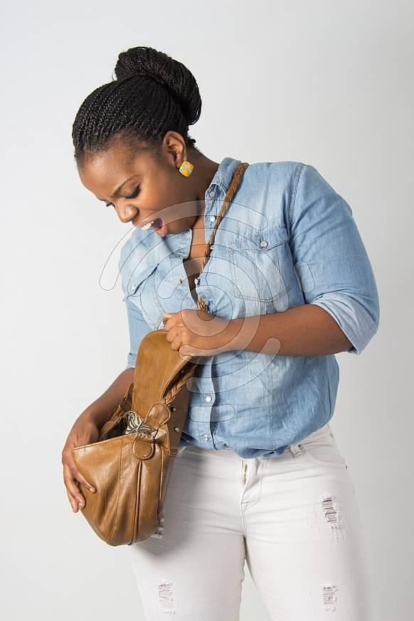 young black female model looking in her handbag looking surprised