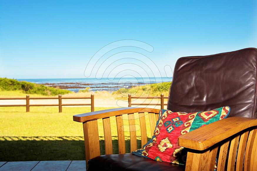 A comfortable leather chair on a patio at a seaside residence or holiday home.