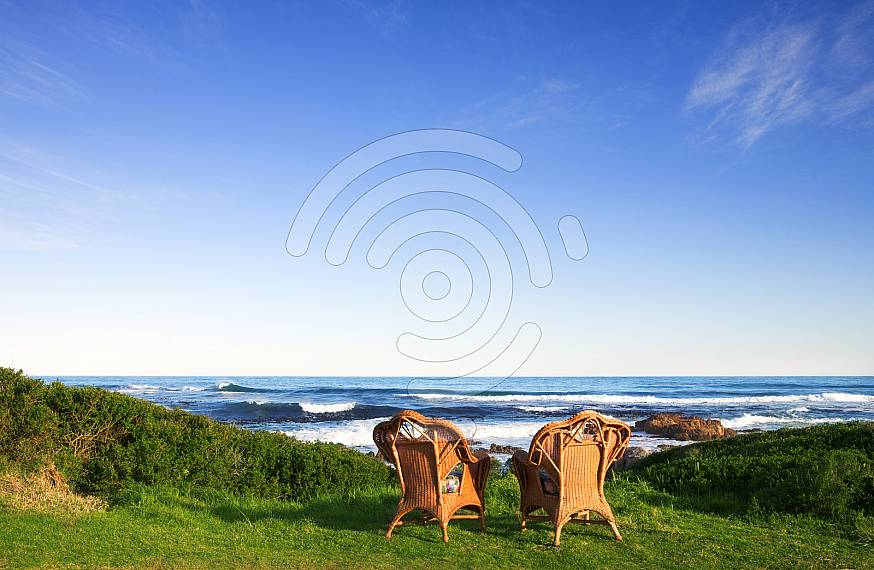 Wicker cane chairs on a lawn next to the sea